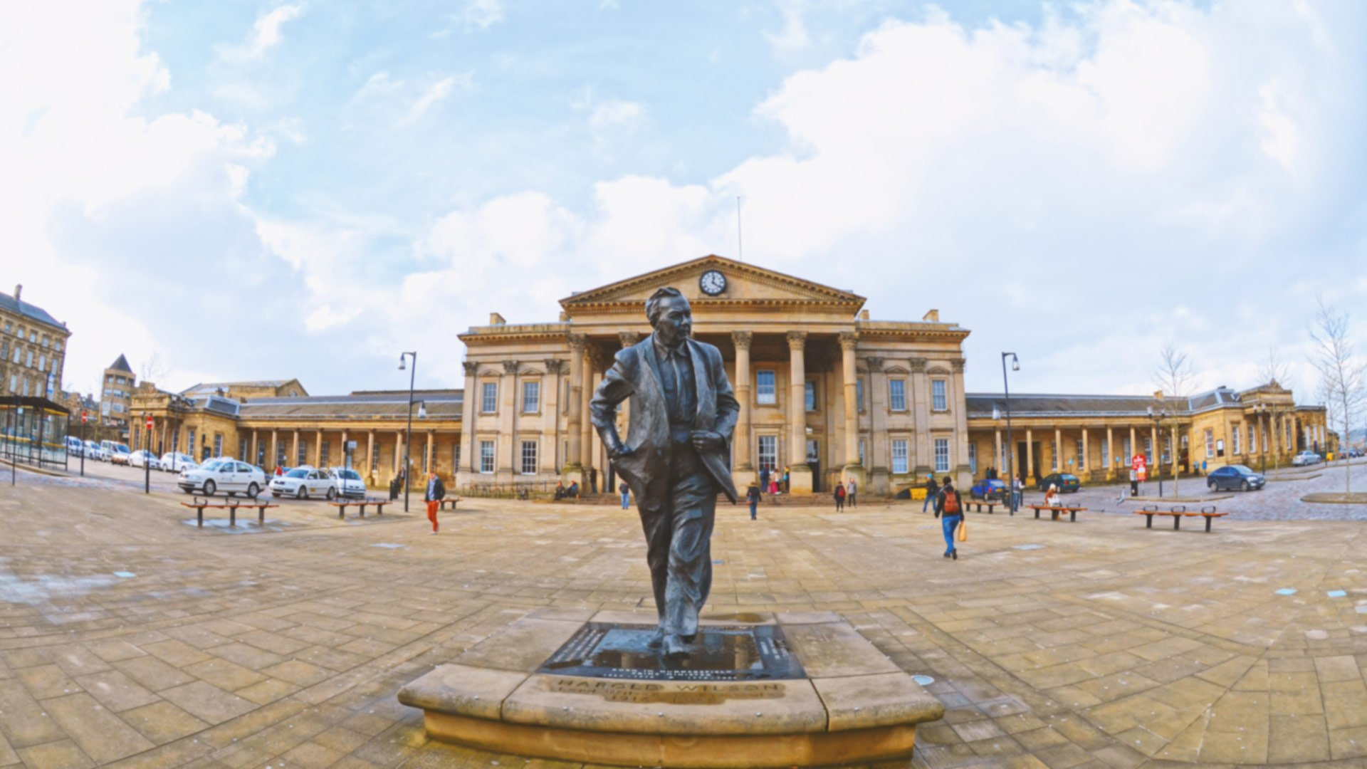 A wide angle view of the Harold Wilson statue outside the railway station