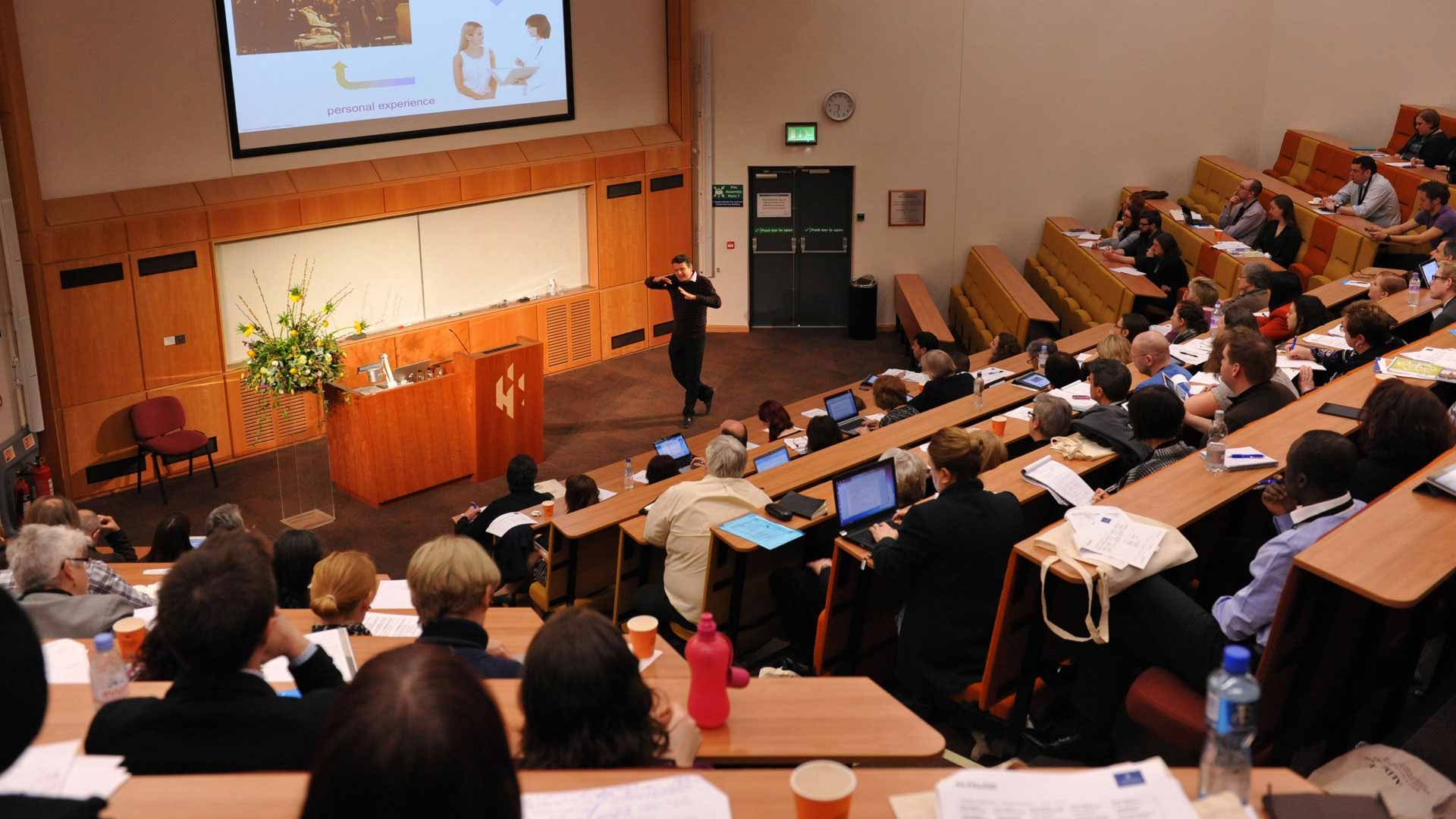 Many students receiving a lecture from a member of staff in a brown and cream lecture hall.