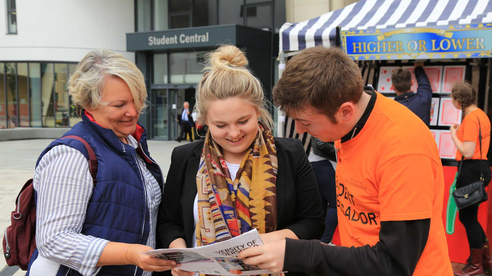 A Student Ambassador helps a parent and potential student look through the open day booklet.