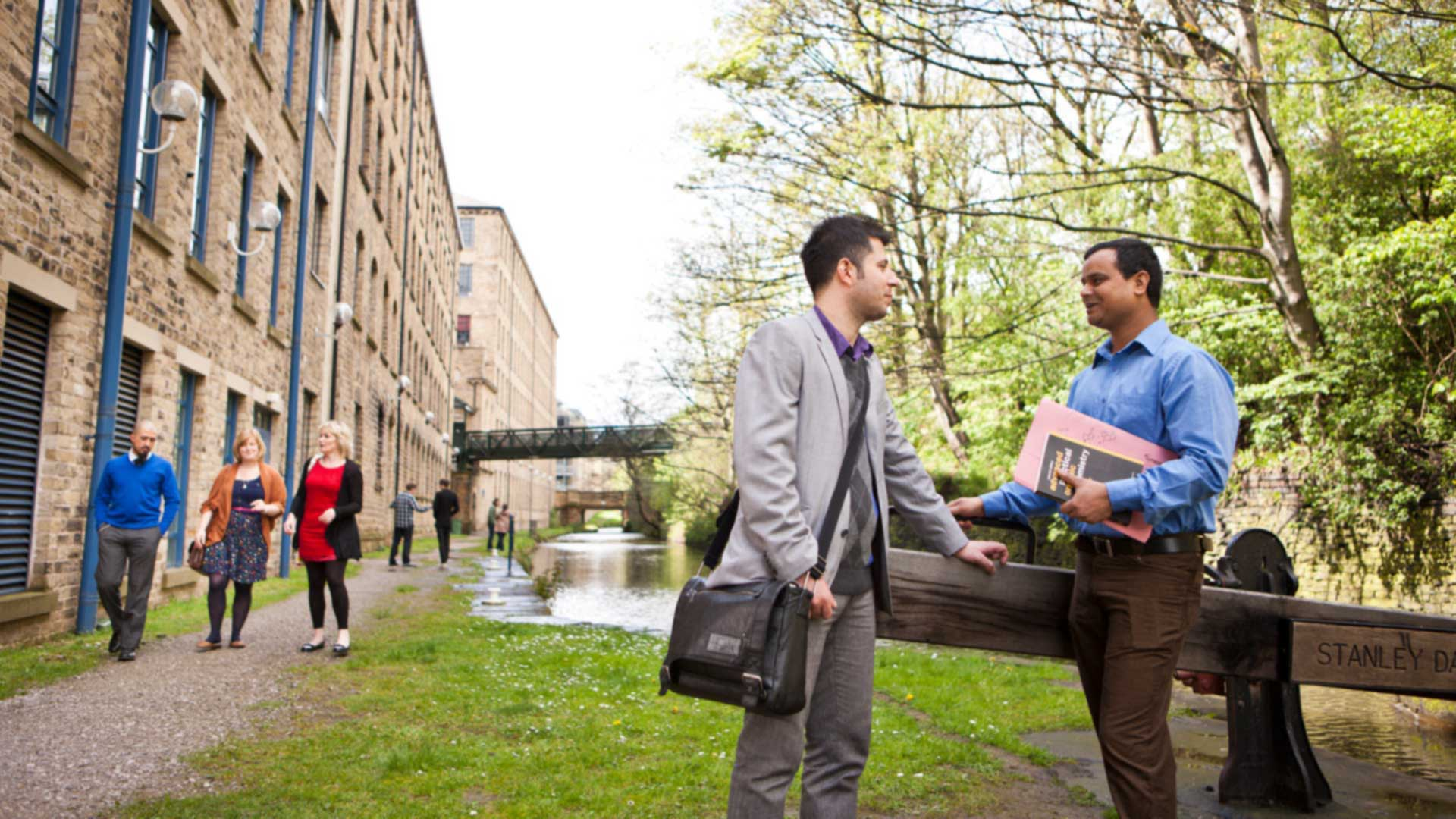 Two students stand chatting next to the canal behind one of the canalside buildings. Other students walk in the background.